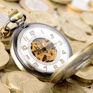 Concept of time is money, old watch on a pile of coins