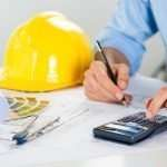 Close Up Of Male Architect Drawing On Blueprint And Using Calculator