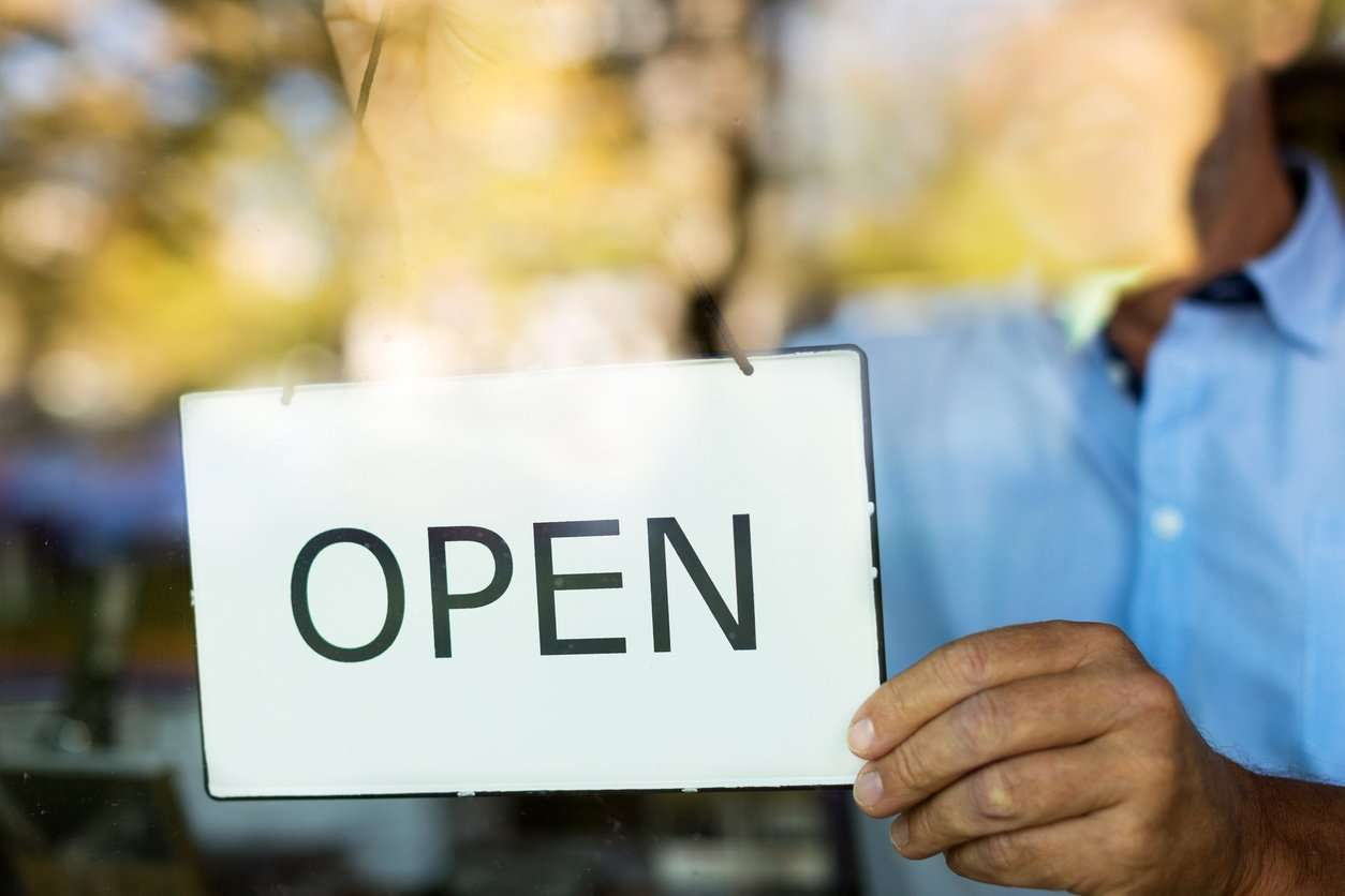 small business owner holding open sign
