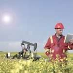 An image fromt the oil and gas industry of an oil worker in a canola field using a tablet PC.
