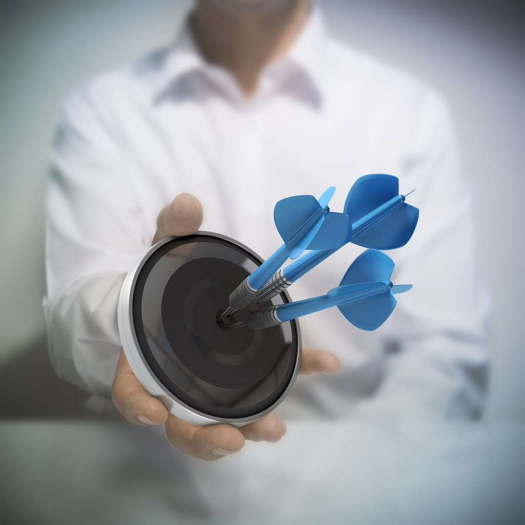 Man holding on black target with three blue darts hitting the center. Concept image for illustration of Marketing and advertising success or self confidence.