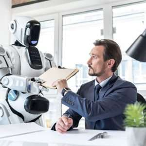 Futuristic helper. Low angle of serious middle-aged businessman sitting at table in office while big robot is passing him important documents